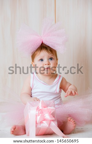 beautiful little girl with a big bow on her head with a gift