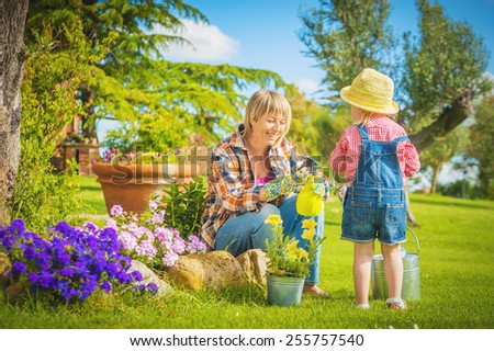 Beautiful little girl with a smile helps his mother in the work of gardening