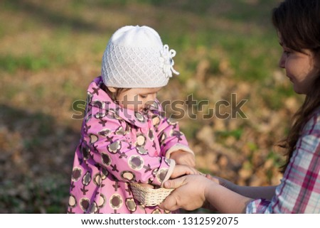 Beautiful  little girl with admiration considers Easter eggs on the spring background