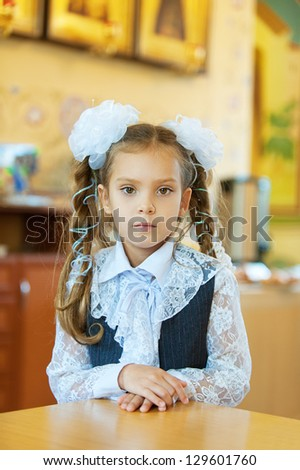 Beautiful little girl with big white bows around table.