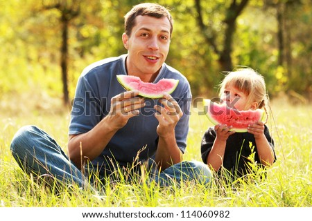 beautiful little girl with dad in nature eating watermelon