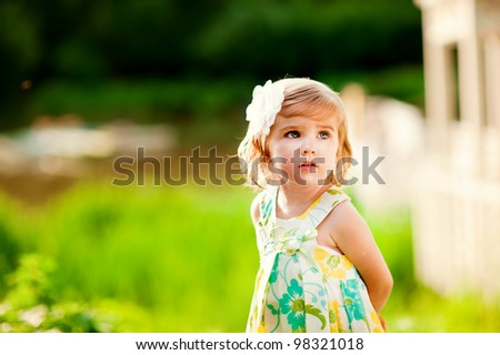 Beautiful little girl with flower on her head outdoors in sunny day