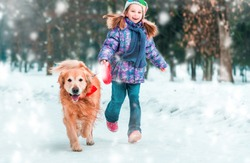 beautiful little girl with her dog on the snow in winter