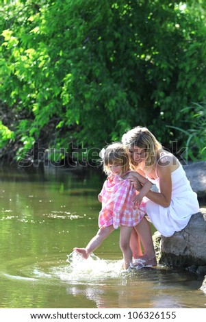 Beautiful little girl with her mother on the nature