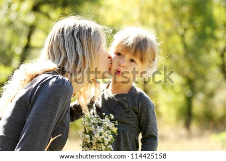 beautiful little girl with her mother outdoors