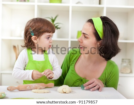 Beautiful little girl with mother cooking - stock photo