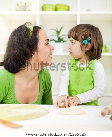 Beautiful little girl with mother cooking