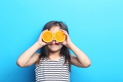 Beautiful little girl with orange on blue background