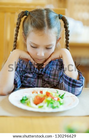 Beautiful little girl with pigtails sitting on table in restaurant and looks at prepared dish.