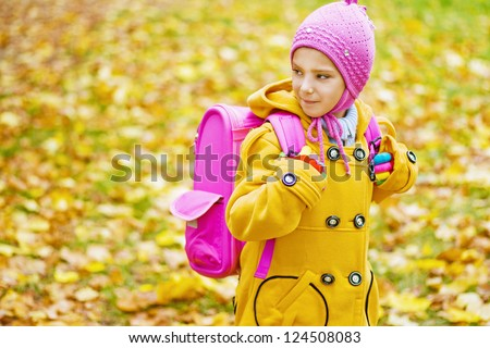 Beautiful little girl with pink backpack goes to school in yellow autumn park.
