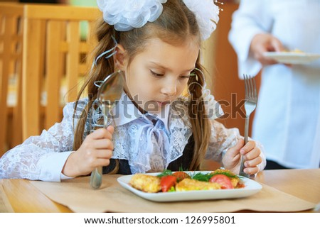 Beautiful little girl with spoon and fork wants to eat tasty dish.