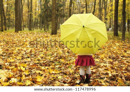 beautiful little girl with umbrella in the autumn forest