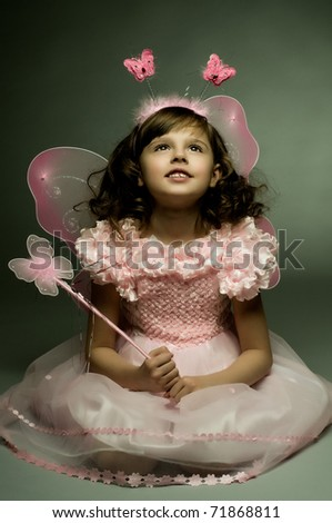 beautiful  little girl with wings, sit and  smile on dark background