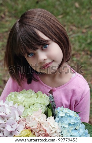Beautiful little girl witha  bunch of pastel colored Hydrangeas for her mother on Mother's Day. - stock photo