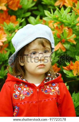 Beautiful little girl 3 years old wearing glasses  in denim jeans cap and red jacket on flower background