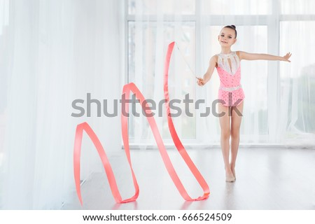 Beautiful little gymnast girl in pink sportswear dress, doing rhythmic gymnastics exercise Spirals with art ribbon in fitness class. Sport, training, stretching, active lifestyle concept