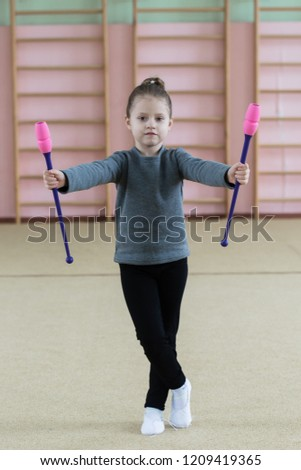 Stock Photo Beautiful little gymnast girl, performing art gymnastics element with mace in fitness class. Sport, training, stretching, active lifestyle concept