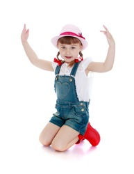 Beautiful little hairy girl with short bangs and braids in which the braided bows on his knees in the hat, denim overalls and red boots - isolated on white background
