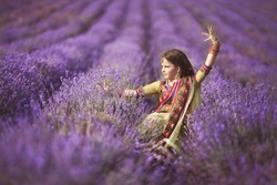 Beautiful little indian girl outdoors in lavender field, Aromatherapy. Adorable baby girl dancing at lavender flowers. Happy indian kid in traditional sari. Cute girl bellydancer.