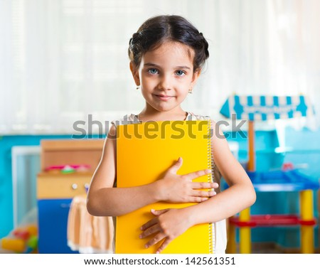 Beautiful little latin girl portrait with book in daycare