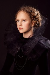 Beautiful little red-haired girl in a medieval queen costume. Black on black. Stylization.