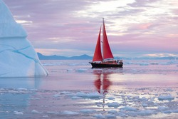 Beautiful little red sailboat in the arctic next to a massive iceberg showing the scale in pink dawn light. Ilulissat, Disko Bay, Greenland.