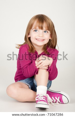 beautiful little smiling girl sitting on the ground