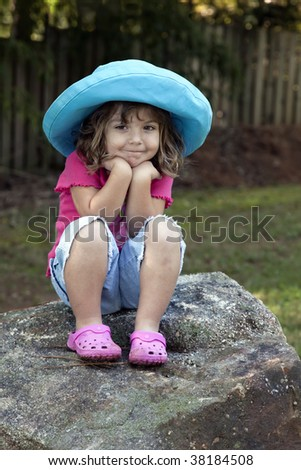 Beautiful little smiling three year old girl sitting outdoors on large rock while wearing blue jean shorts, a pink top and shoes, and a blue hat