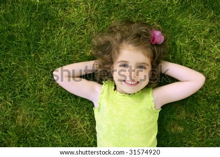 Beautiful little toddler girl happy lying on the green grass - stock photo