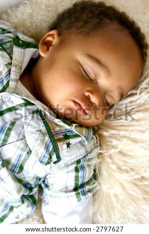 Beautiful little toddler of mix parentage, fallen asleep on a sheep skin rug.