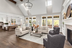 Beautiful living room and kitchen in new traditional style luxury home. Features vaulted ceilings and elegant furnishings.