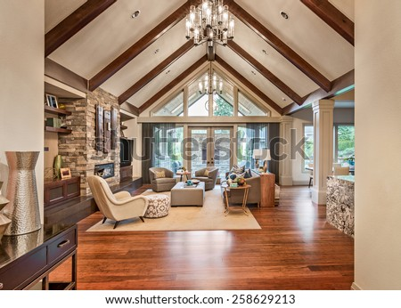 Beautiful living room in luxury home with hardwood floors, tv, fireplace, and vaulted ceiling