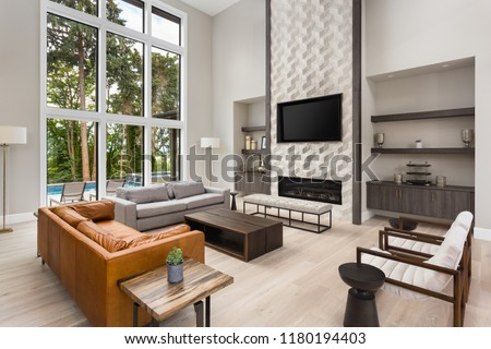 Beautiful living room in new luxury home wall of windows, floor to ceiling fireplace surround, hardwood floors, and exterior view of pool and trees #1180194403