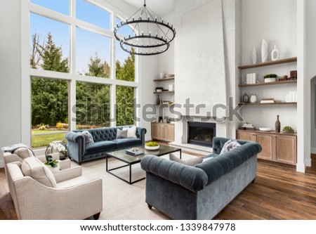Beautiful living room in new luxury home with large bank of windows showing exterior view.  #1339847978