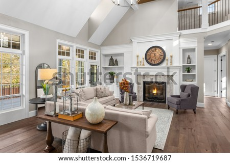 Beautiful living room in new traditional style luxury home. Features vaulted ceilings, fireplace with roaring fire, and elegant furnishings. Stock photo ©