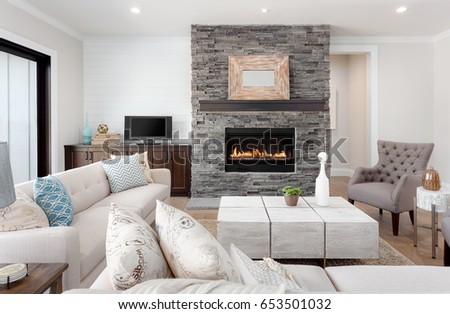 Beautiful living room interior with hardwood floors and fireplace in new luxury home. Couches at right angles face armchairs and fireplace surround stretches to ceiling and is bordered by credenza. - Shutterstock ID 653501032