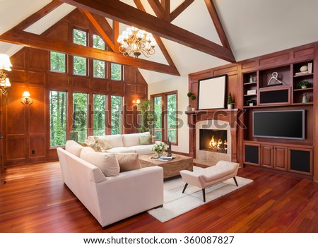 Beautiful living room interior with hardwood floors and fireplace in new luxury home. Includes built-ins with television and vaulted ceilings. Lush green trees fill the exterior view.