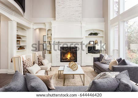 Beautiful living room interior with hardwood floors and fireplace in new luxury home. Large bank of windows hints at exterior view #644446420