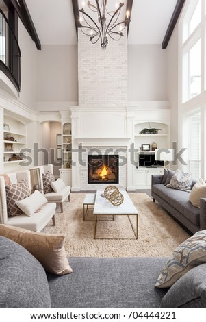 Beautiful living room interior with hardwood floors and fireplace in new luxury home, with large light fixture. Vertical Orientation.