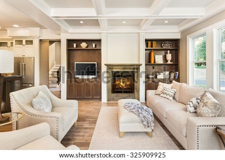 Beautiful living room interior with hardwood floors, coffered ceiling, and roaring fire in fireplace, in new luxury home #325909925