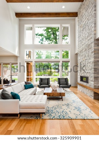 Beautiful living room interior with hardwood floors, huge bank of windows, tall vaulted ceiling, and fireplace in new luxury home #325909901