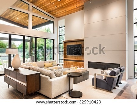 Beautiful living room interior with hardwood floors, vaulted ceiling, and fireplace in new luxury home