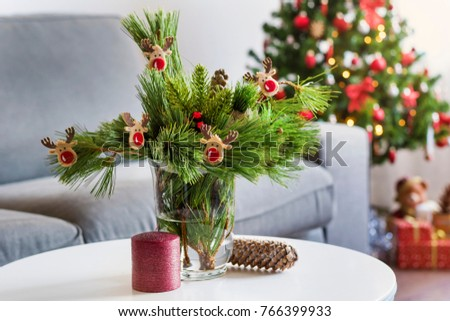 Beautiful Living Room with Christmas Tree ,Presents under it and Pine Branches Bouquet on the Table #766399933