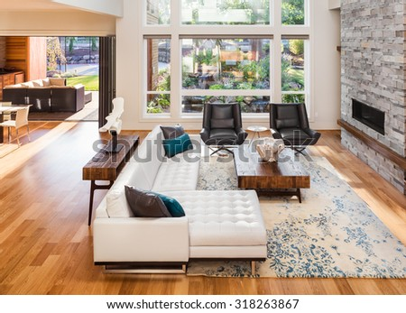 Beautiful living room with hardwood floors and fireplace in new luxury home. View of outdoor patio
