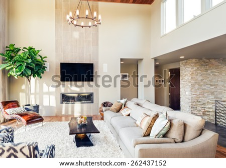 Beautiful living room with hardwood floors, tv, chandelier, and fireplace #262437152