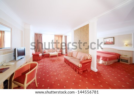 Beautiful living room with soft striped sofas and bedroom with red carpet flooring.