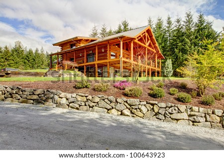 Beautiful Log cabin on the hill with large decks. - stock photo