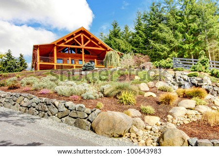 Beautiful Log cabin on the hill with waterfall and flowers.