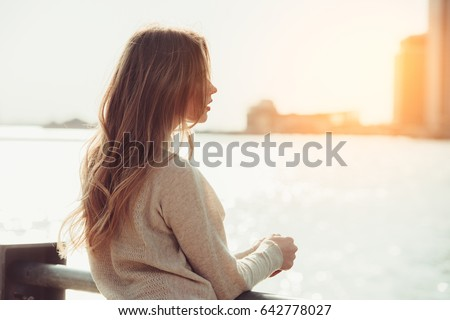 Beautiful lonely girl dreaming and thinking while waiting for date in the city ocean pier at sunset time.