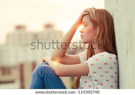 beautiful lonely girl sitting on the roof - stock photo